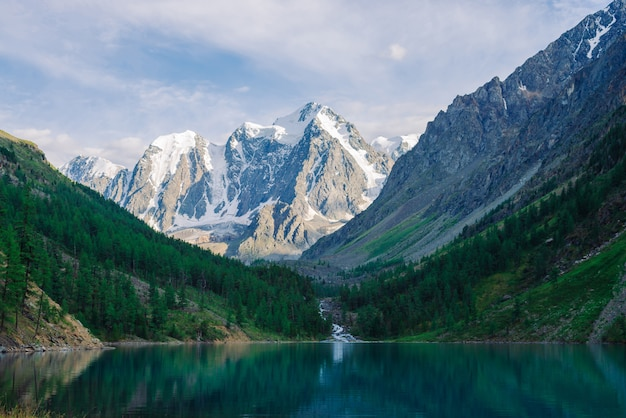 Cudowne gigantyczne zaśnieżone góry. creek płynie z lodowca do górskiego jeziora. odbicie w wodzie na wyżynach. biały śnieg na grzbiecie. niesamowity klimatyczny krajobraz majestatycznej przyrody.