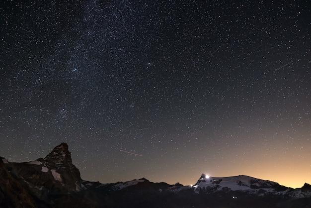 Cudowne gwiaździste niebo nad szczytem matterhorn (cervino) i lodowcami monte rosa