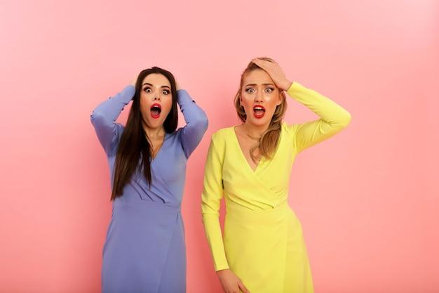 Cudowne jasne panie w letnich stylowych sukienkach, żółto-niebieskich. blondynka i brunetka z dużymi czerwonymi ustami i nowoczesną fryzurą. zgrabne gorące ciała, seksowne modelki. zdjęcia w studio na tle pinezki