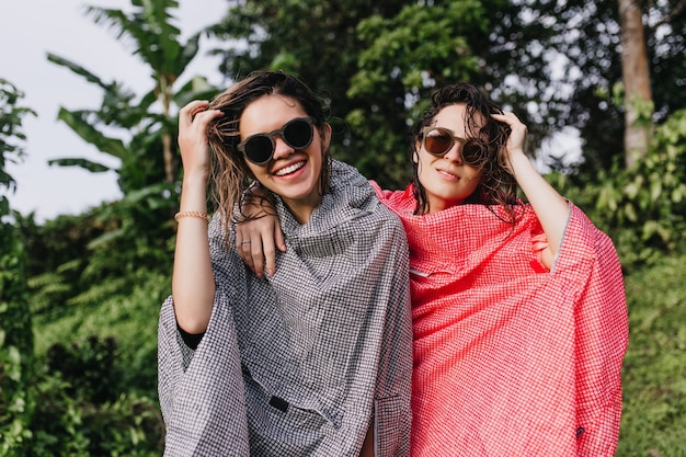 Cudowne kobiety z mokrymi włosami śmieją się, pozując na naturze. oszałamiające panie w płaszczach przeciwdeszczowych lubiące wędrówki.