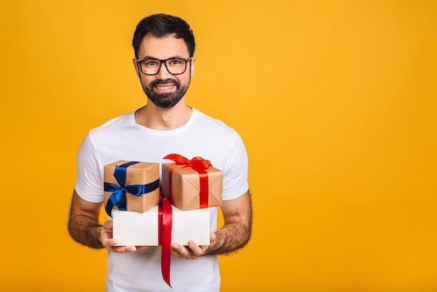 Cudowne prezenty! urocze zdjęcie atrakcyjnego brodatego mężczyzny z pięknym uśmiechem, trzymając pudełka na prezent urodzinowy na białym tle na żółtym tle.