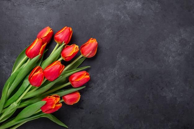 Cudowne wiosenne tulipany na ciemnym kamiennym stole. tło wiosna. widok z góry. skopiuj miejsce