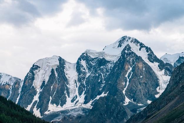 Cudowne zbliżenie lodowca słonecznego. promień słońca na śnieżnym szczycie góry. skalisty grzbiet ze śniegiem w słoneczny poranek.