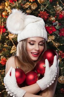 Cudowne zdjęcie noworoczne. piękna dziewczyna w kapeluszu i rękawiczkach trzyma czerwone kulki