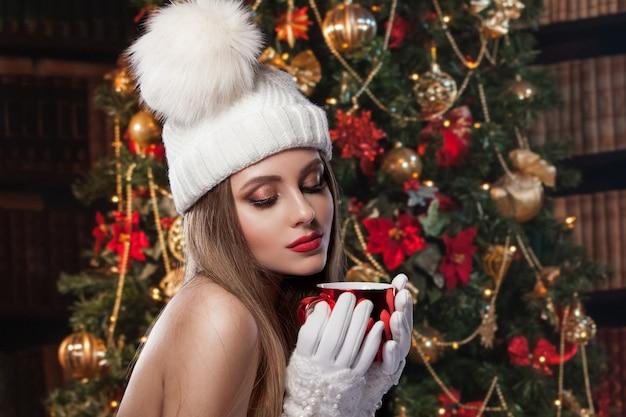 Cudowne zdjęcie noworoczne. piękna dziewczyna w kapeluszu i rękawiczkach trzyma czerwony kubek
