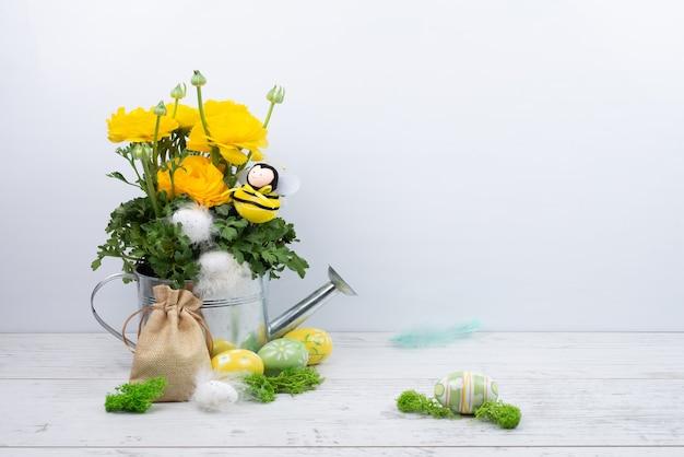 Cudowne żółte jaskry jaskier w metalowej konewce, pszczoła, pisanki z piórami, płócienna torba.