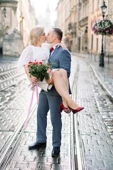 Cudownie całuje się dojrzała para na świeżym powietrzu na starym mieście, uśmiechając się i patrząc na siebie