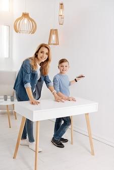 Cudowny nastrój. pozytywnie szczęśliwi zachwyceni mama i syn stojący razem i patrząc na ciebie, korzystając z nowoczesnych inteligentnych technologii