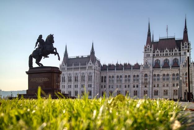 Cudowny pomnik konny rakoczi ferenc przed węgierskim budynkiem paliamentowym z zieloną trawą w budapeszcie na węgrzech.