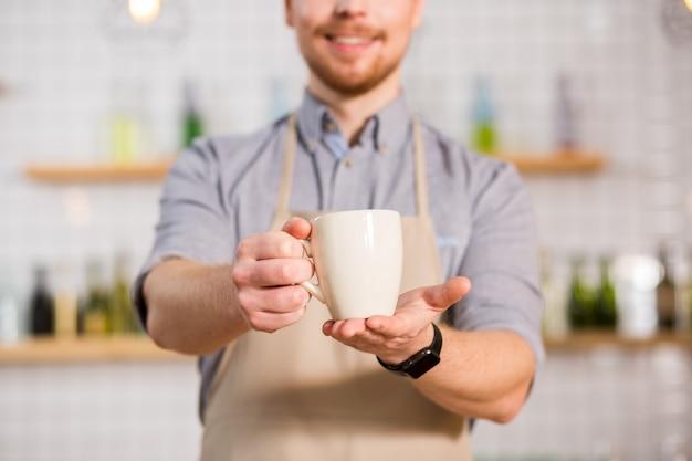 Cudowny smak. selektywne skupienie się na filiżance herbaty trzymanej przez miłego przystojnego, przyjemnego mężczyznę podczas pracy w kawiarni