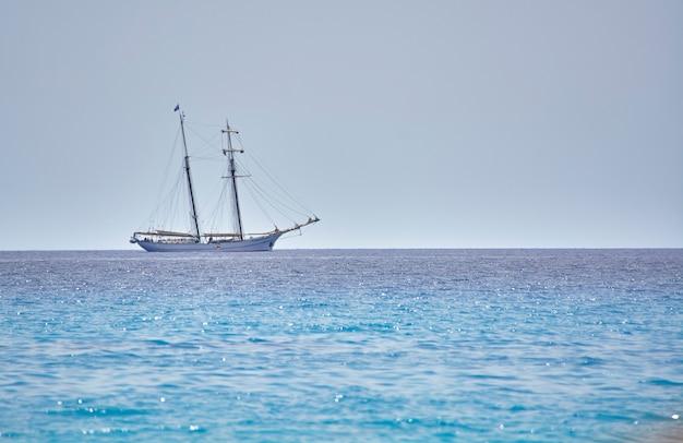 Cudowny statek płynie po krystalicznym i błękitnym morzu na linii horyzontu