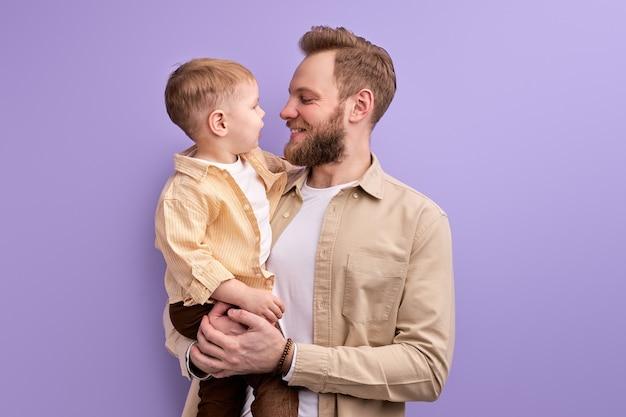 Cudowny syn i młody ojciec na białym tle na fioletowej ścianie studio, portret kaukaskiej rodziny bez mamy.