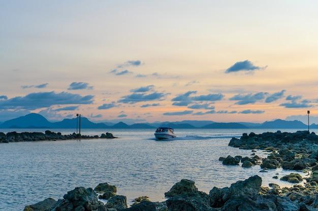 Cudowny zachód słońca nad brzegiem morza, kolory zachodzącego słońca i sylwetka wyspy na wodzie. niesamowity tropikalny zachód słońca.