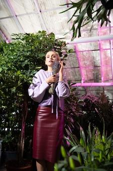 Cudowny zapach. przyjemna spokojna kobieta trzymająca bukiet i wąchająca kwiaty