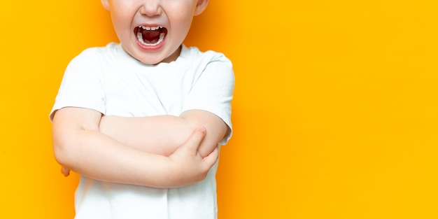 Cue mały 3-letni chłopiec stoi i głośno krzyczy z otwartymi ustami, z założonymi na piersi ramionami, w białym t-shircie