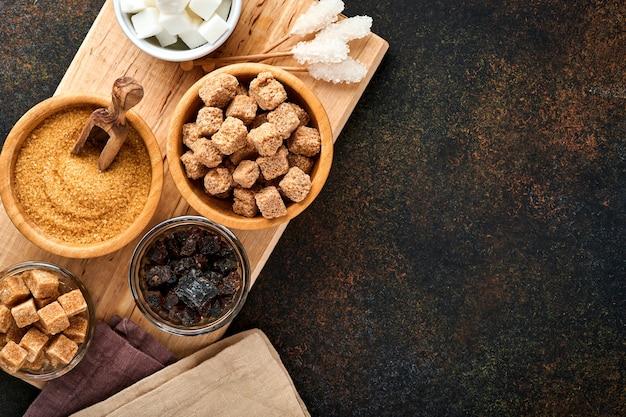 Cukier biały, cukier trzcinowy w kostkach, karmel w bambusowej misce na ciemnobrązowym betonowym stole
