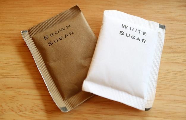 Cukier brązowy i cukier biały w papierowych torebkach