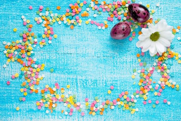 Cukier cukiernik tło wielkanoc i jaja przepiórcze na drewnianym stole.
