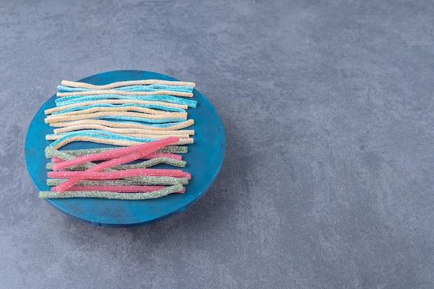 Cukier puder na cukierku z lukrecji na talerzu na marmurowym stole