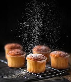 Cukier sproszkowany wylewa się na muffinkę