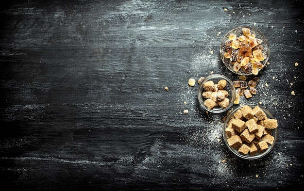 Cukier trzcinowy brązowy. na czarnym rustykalnym stole.