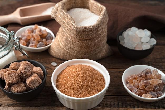 Cukier trzcinowy, cukier rafinowany, cukier biały i lizak na tle drewnianych.