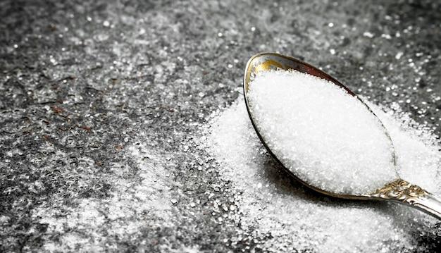 Cukier w łyżeczce. na rustykalnym tle.