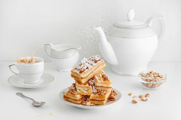 Cukier w proszku wylewa się na wafle wiedeńskie z orzechami i rozlewa kawę na stole śniadaniowym