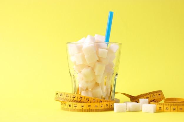 Cukier w szklance i miarka na kolorowym tle