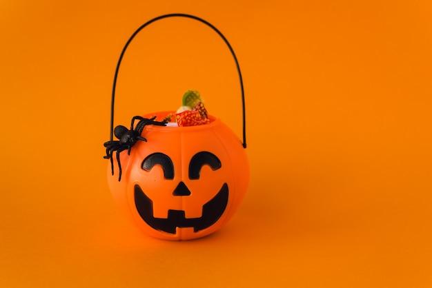 Cukierek albo psikus na halloween. wiadro dyni ze słodyczy i pająków na pomarańczowym tle. słodycze dla dzieci na halloween. copyspace
