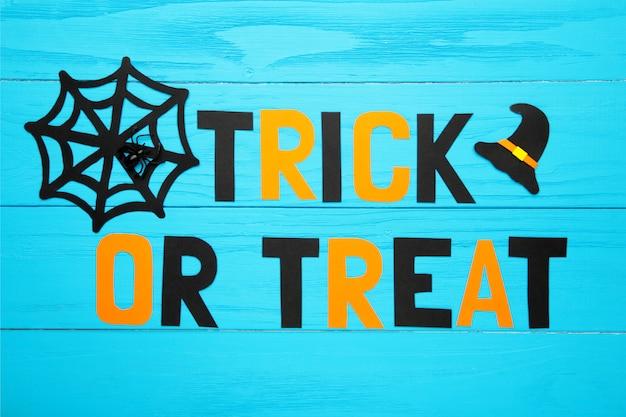 Cukierek albo psikus napis z dekoracją halloweenową na niebieskiej powierzchni