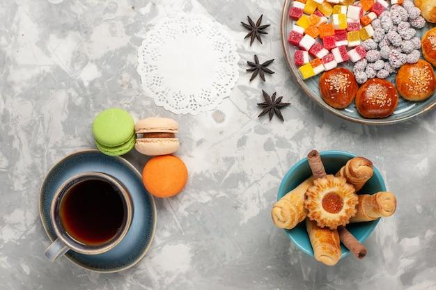 Cukierki cukrowe z widokiem z góry z małymi słodkimi bułeczkami na jasnobiałej powierzchni