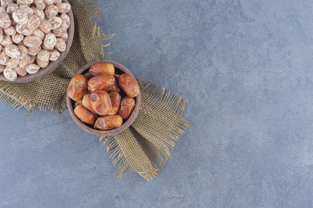 Cukierki cynamonowe i owoce daktylowe na marmurowym tle.