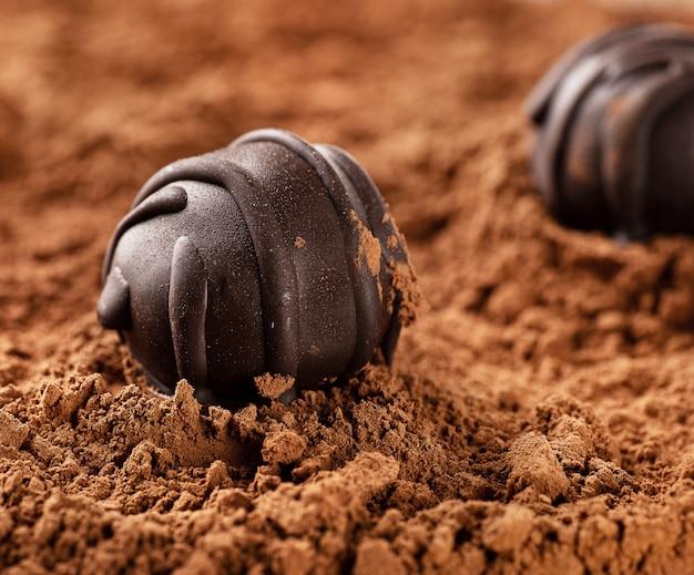 Cukierki czekoladowe bez cukru leżą na kakao.