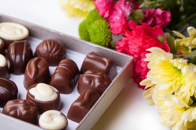 Cukierki czekoladowe i kwiaty na białym