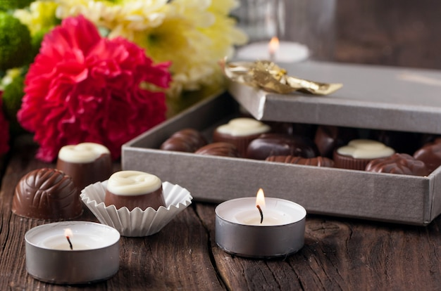 Cukierki czekoladowe, świece i kwiaty