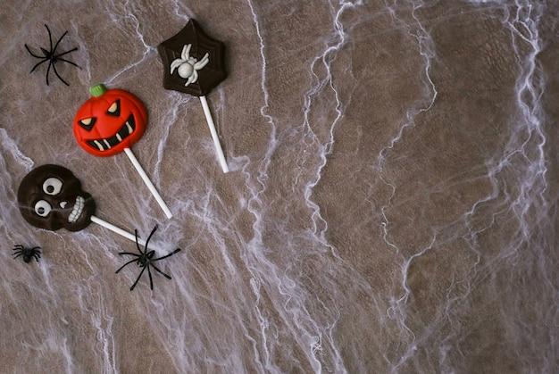 Cukierki czekoladowe w kształcie czaszki, dyni jacka i pająka na tle pajęczyny. koncepcja halloween