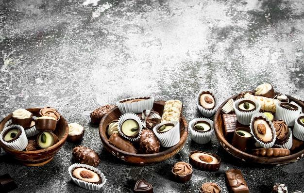 Cukierki czekoladowe w miseczkach. na rustykalnym tle.