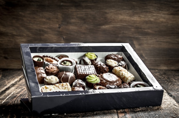 Cukierki czekoladowe w pudełku. na drewnianym tle.