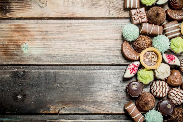 Cukierki czekoladowe z orzechami i różnymi nadzieniami. na drewnianym tle.