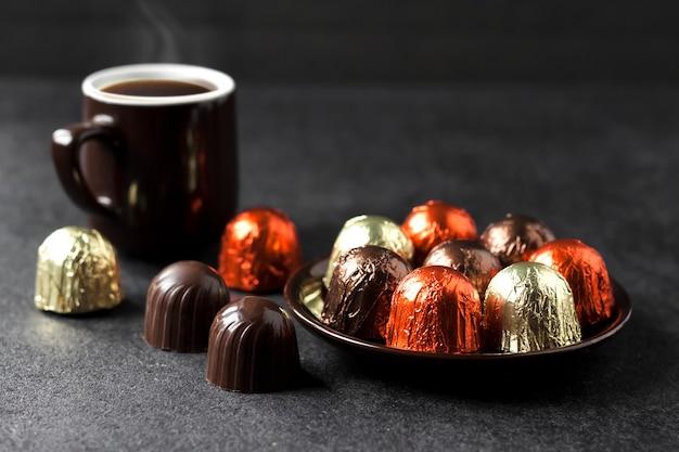 Cukierki czekoladowe zawinięte w wielobarwną folię na talerzu i filiżankę gorącej kawy na czarnej powierzchni z miejscem na kopię