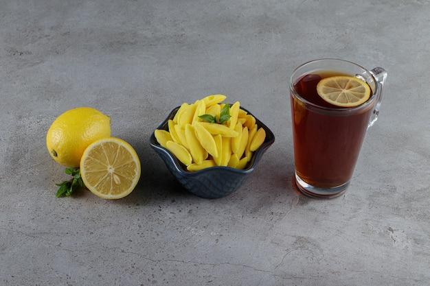 Cukierki do żucia w kształcie banana ze szklaną filiżanką gorącej herbaty i świeżą cytryną