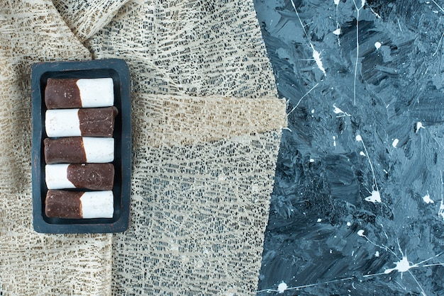 Cukierki dwukolorowe na drewnianym talerzu na obrusie, na niebieskim stole.