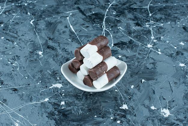 Cukierki dwukolorowe na talerzu na niebiesko.