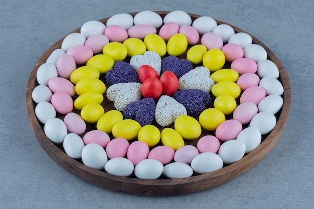 Cukierki i ciasteczka na okrągłej tacy, na marmurowym stole.