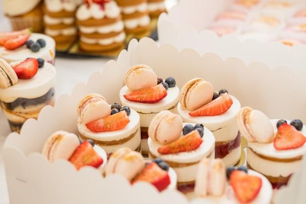 Cukierki i ciasto czekoladowe na stole deserowym na imprezie. ciasto z różnymi jagodami i bezami na stojaku. ciastka, deser z jagodami, batonik na imprezę