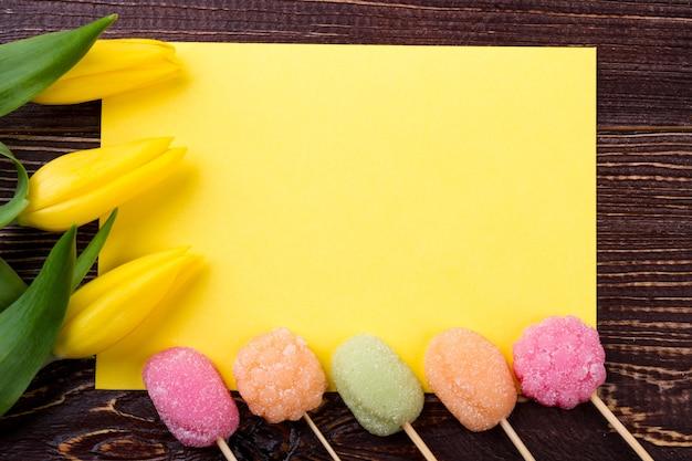 Cukierki i czysty papier. tulipany i słodycze na drewnie. bądź bystry i kreatywny. kolorowa i smaczna niespodzianka.