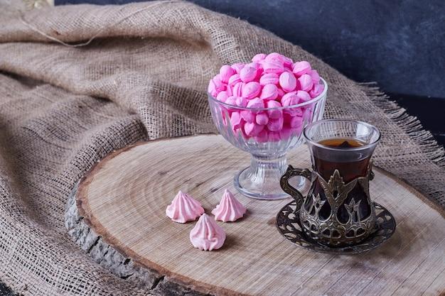 Cukierki karmelowe ze szklanką herbaty.