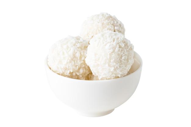Cukierki kokosowe w białej filiżance na białym tle