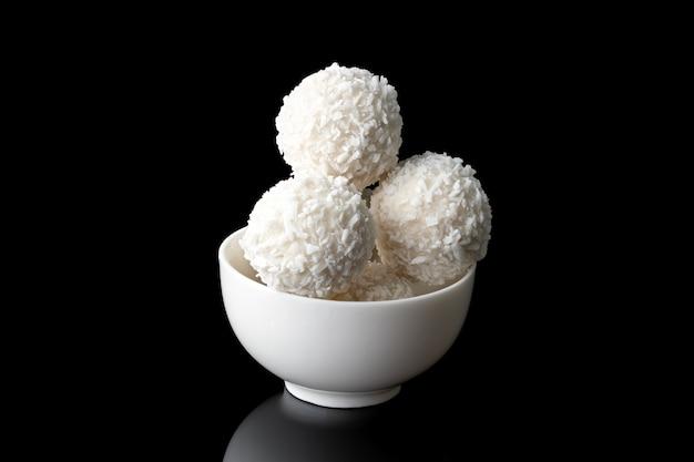 Cukierki kokosowe w białym kubku na białym tle na czarnym tle